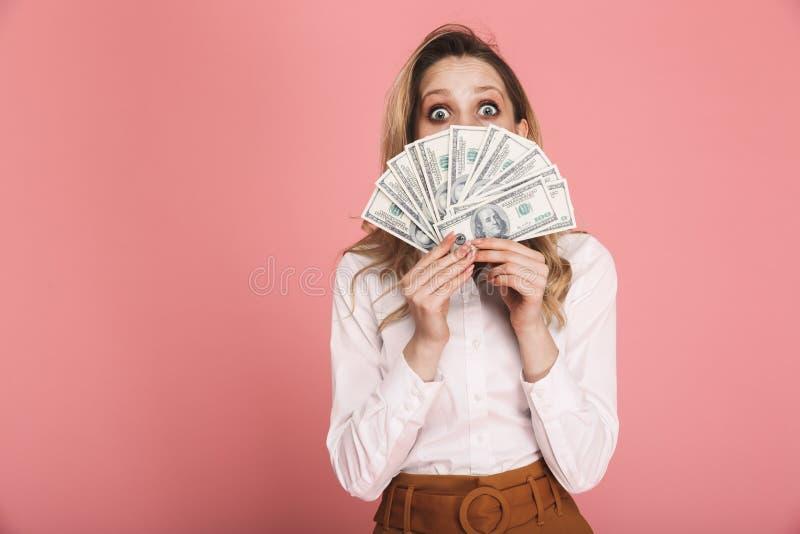 妇女30s画象掩藏时髦的穿戴的,当拿着金钱爱好者被隔绝在桃红色背景时 库存照片