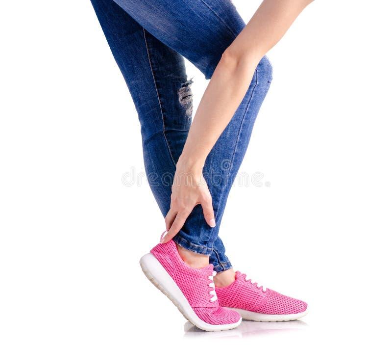 妇女` s腿蓝色牛仔布桃红色运动鞋 免版税库存图片