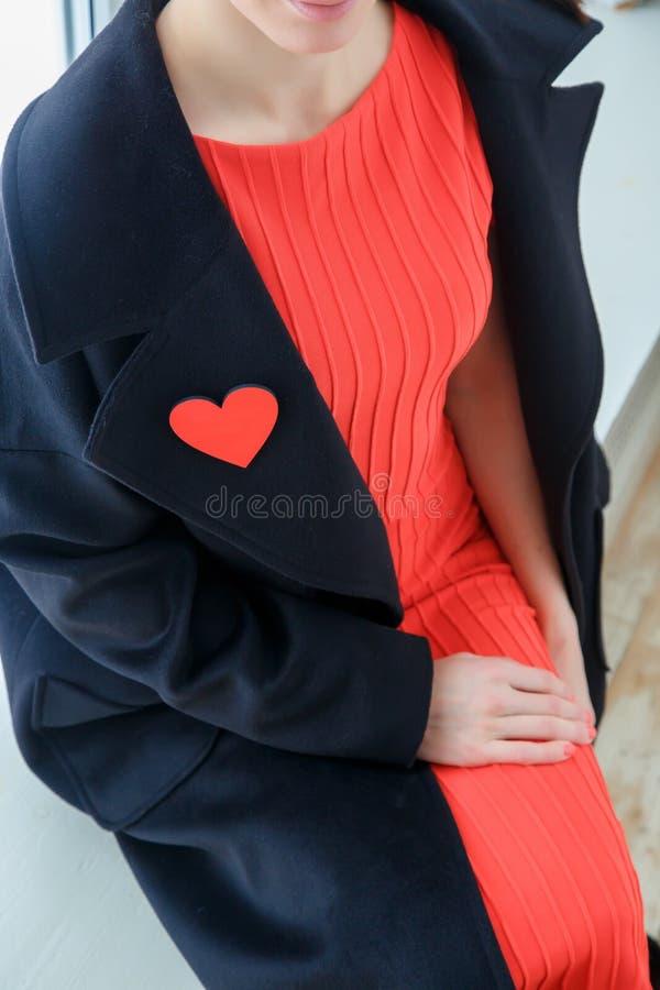 妇女` s衣物细节  以心脏的形式别针在一件黑外套 免版税库存照片