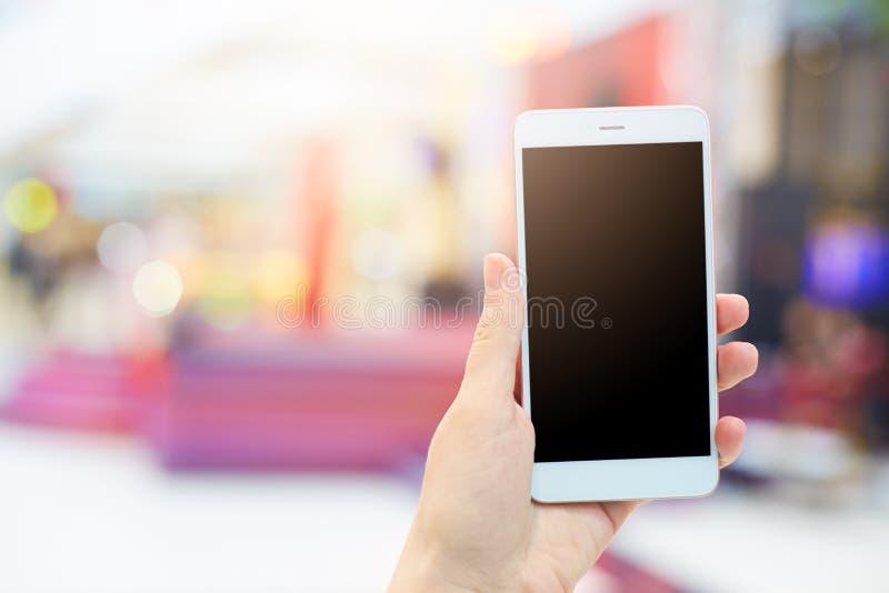 妇女` s递举行现代电子小配件 有白色手机和空白的黑屏幕的无法认出的女性您的广告的 免版税库存照片
