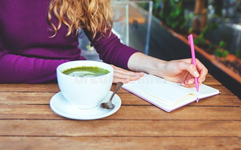 妇女` s递举行letephone和写在笔记本 免版税库存照片