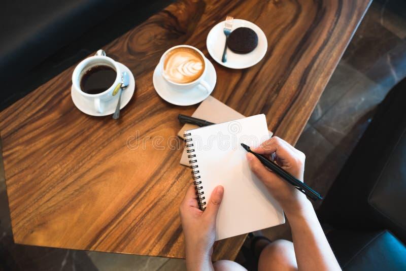 妇女` s递使和写保持向下在有咖啡杯的一个白色空白的笔记本在木桌上在咖啡馆 库存图片