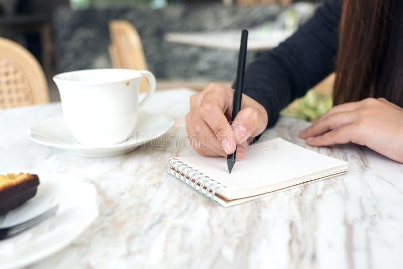妇女` s递写下在有咖啡杯和点心的一个白色空白的笔记本在桌上在咖啡馆 免版税库存图片