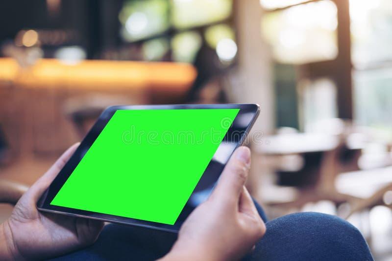 妇女` s递拿着有空白的绿色屏幕的黑片剂个人计算机在大腿有在现代咖啡馆的具体地板背景 免版税图库摄影