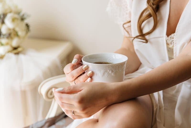 妇女` s递拿着白色茶或咖啡在轻的室背景 早晨时间早餐 免版税库存图片