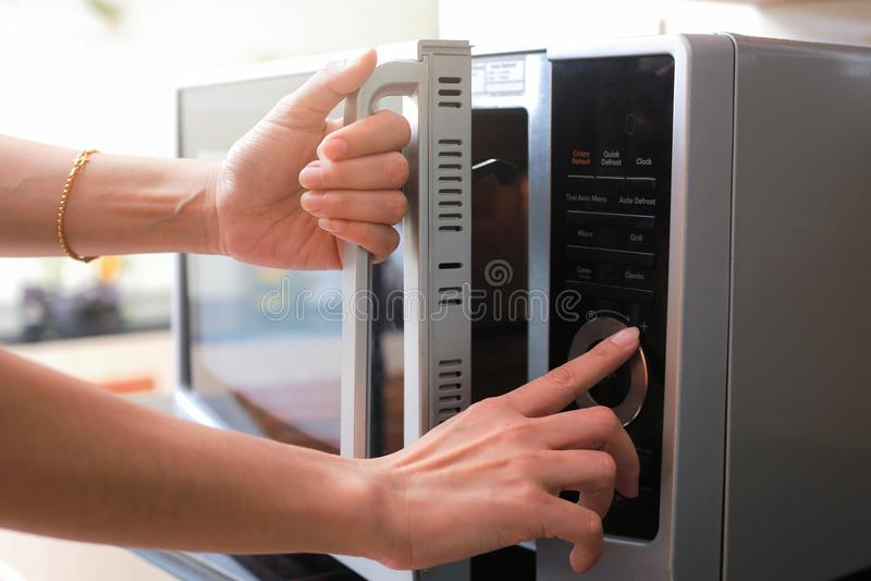 妇女` s递闭合值的微波炉门和准备食物  免版税库存图片