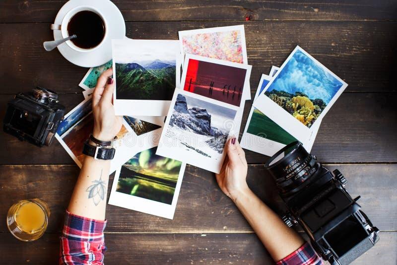妇女拿着打印的照片的` s手 穿戴在红色衬衣,在胳膊的莲花纹身花刺