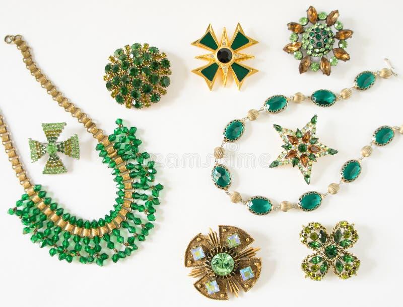 妇女` s首饰 葡萄酒首饰背景 美丽的明亮的假钻石别针、braceletes、项链和耳环在白色 Fl 免版税库存图片