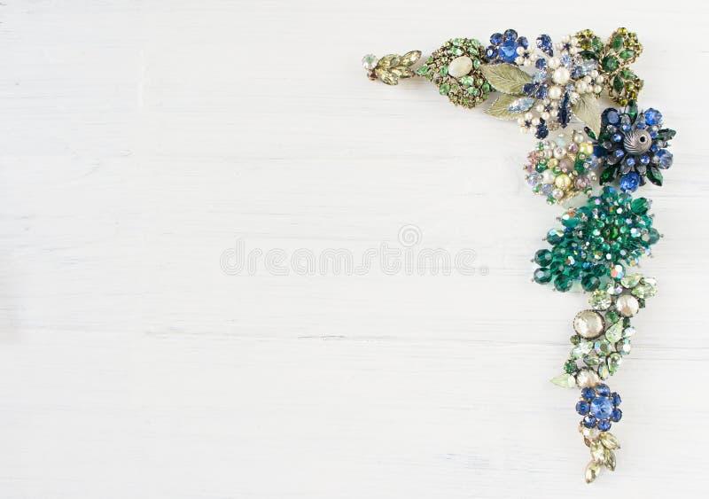 妇女` s首饰 葡萄酒首饰背景 美丽的明亮的假钻石别针、项链和耳环在白色木头 平的位置, t 免版税库存图片