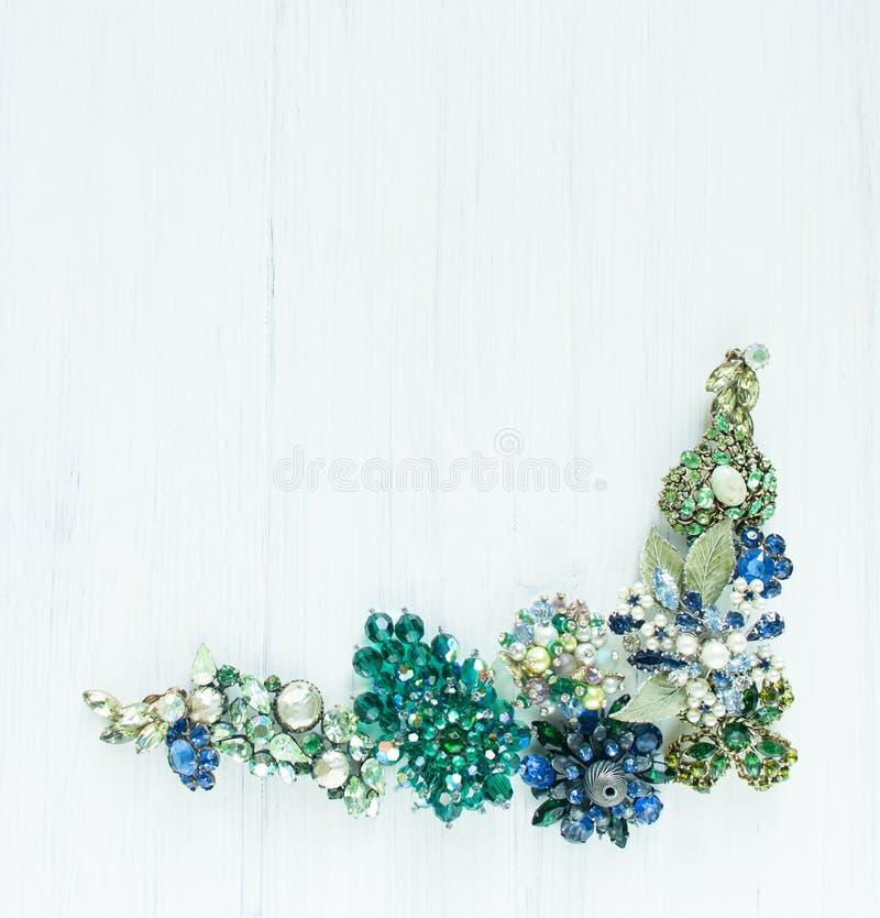 妇女` s首饰 葡萄酒首饰背景 美丽的明亮的假钻石别针、项链和耳环在白色木头 平的位置, t 免版税图库摄影