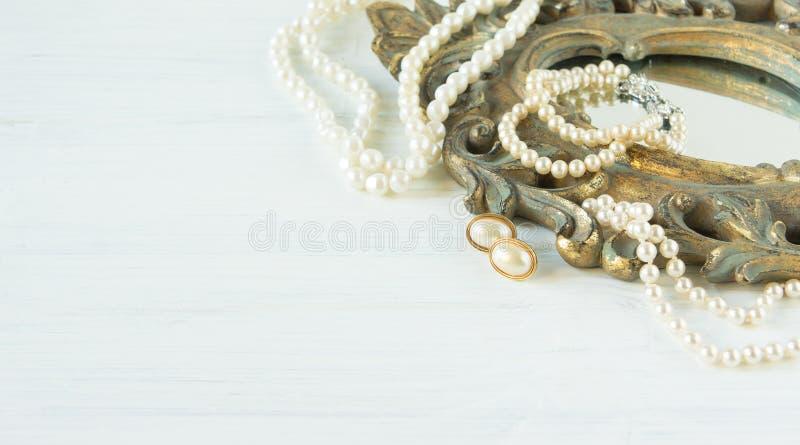 妇女` s首饰 葡萄酒首饰背景 美丽的珍珠项链、镯子和耳环在一个老镜子框架 平的位置, t 免版税库存照片