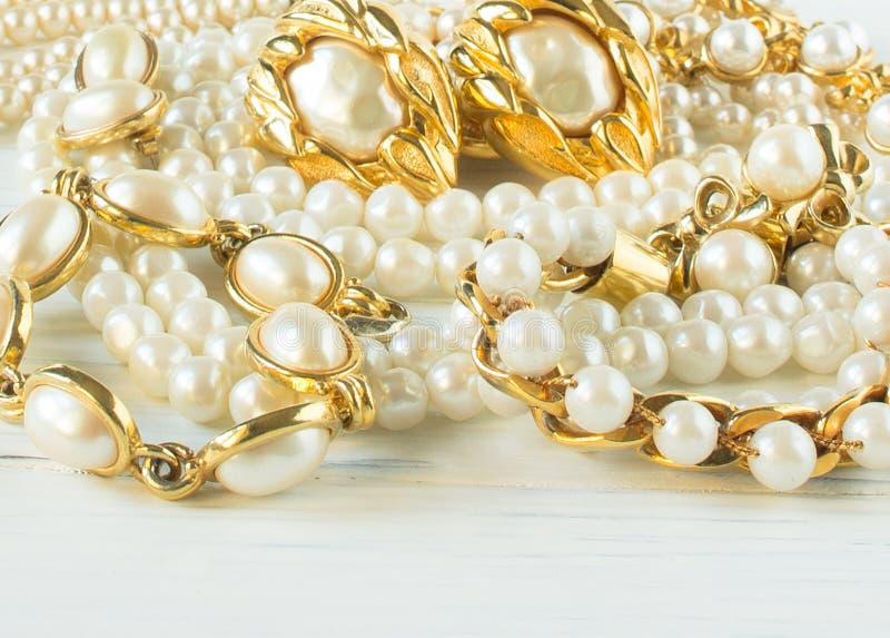 妇女` s首饰 葡萄酒首饰背景 美丽的金和珍珠项链、镯子和耳环在白色木头 平的位置, 库存图片