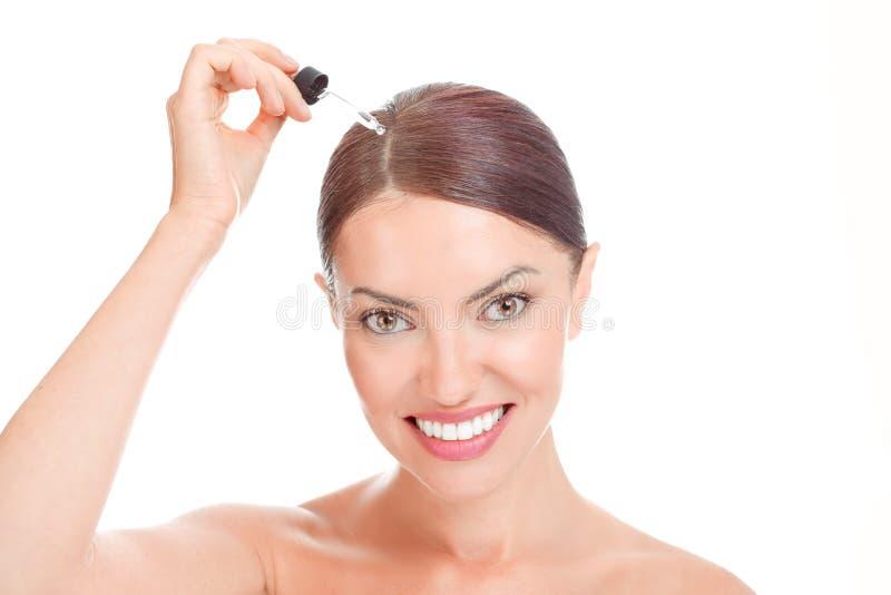 妇女aplying的血清精华,对她的细线的精油 库存照片
