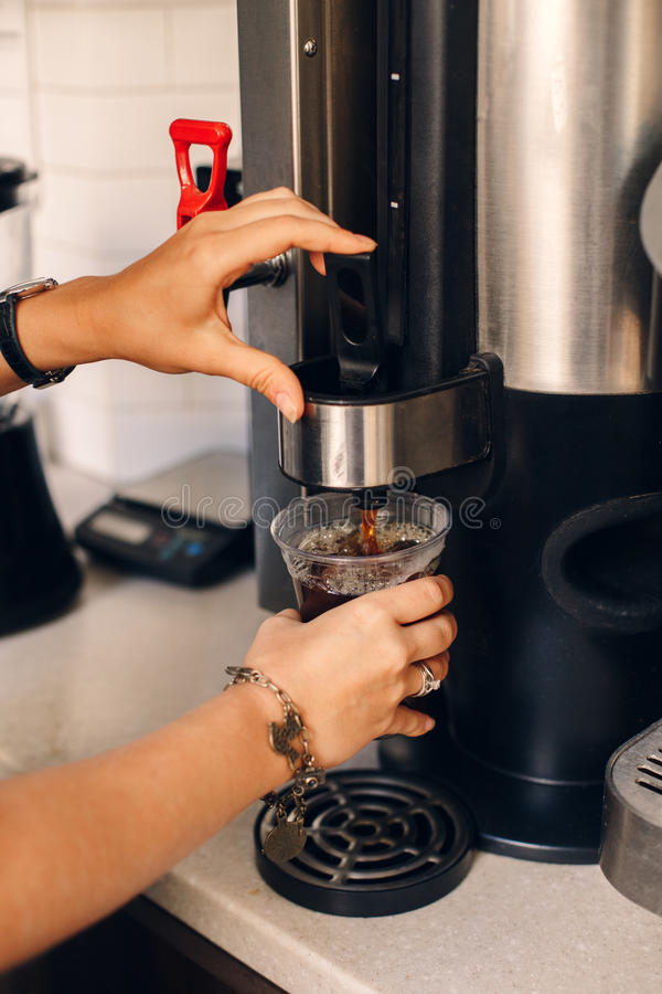 妇女barista递做倾吐的咖啡由在塑料透明杯子的咖啡机器 免版税库存照片