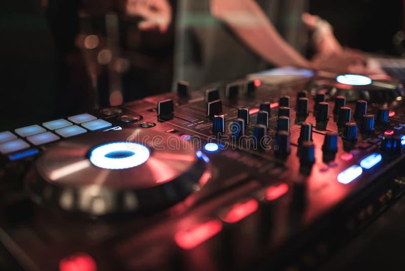 妇女DJ的手扭捏在dj ` s甲板的各种各样的轨道控制在夜总会 免版税库存照片