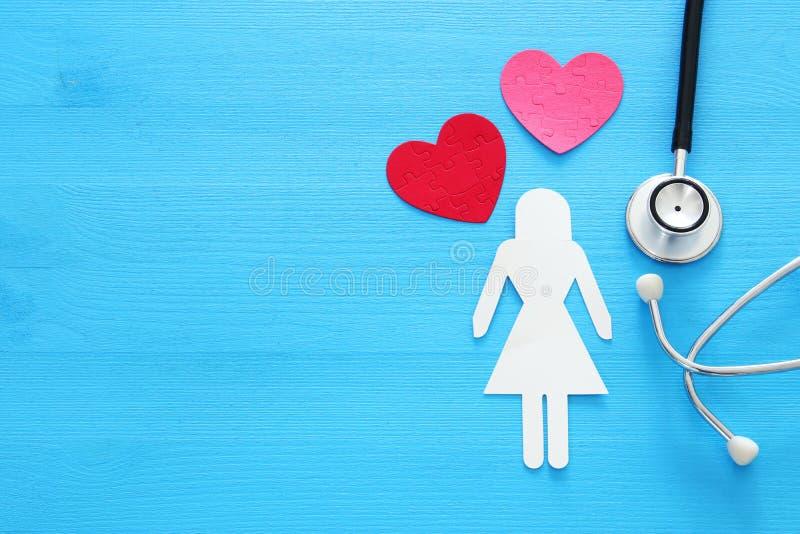妇女healf保险 听诊器和妇女形象的概念图象在木桌上 顶视图 免版税库存图片