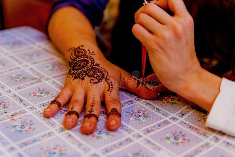 妇女mehendi艺术家在手上的绘画无刺指甲花 库存照片