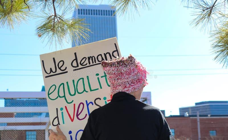 妇女n桃红色有回到照相机的猫帽子站立反对与我们要求平等变化在妇女的标志的城市地平线 图库摄影