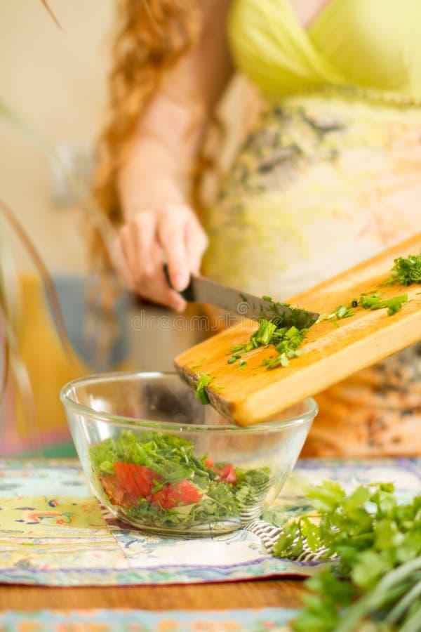 妇女s递切新鲜的葱,莳萝,在厨房焦点的荷兰芹在绿色菜 免版税库存图片