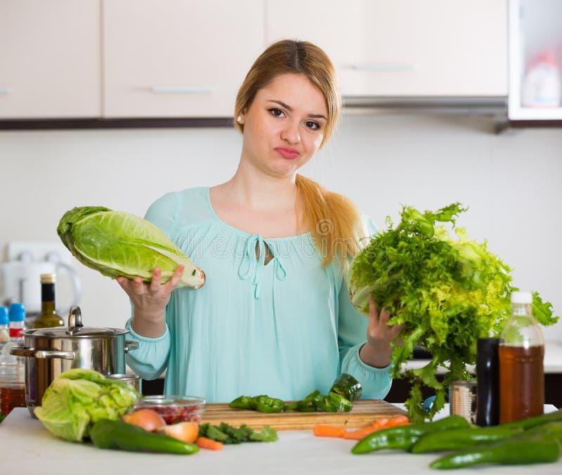 年轻主妇疲倦了于烹调菜在国内厨房里 免版税库存照片