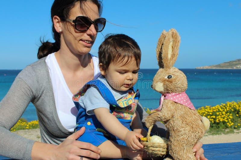 妈咪和使用在与复活节兔子的草的男婴 库存照片