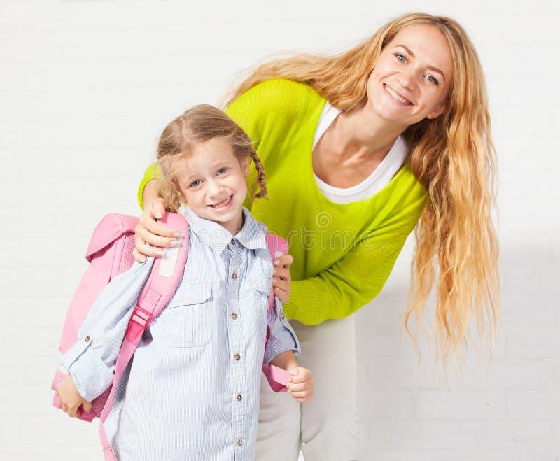 妈咪帮助她的女儿准备好学校 免版税库存照片