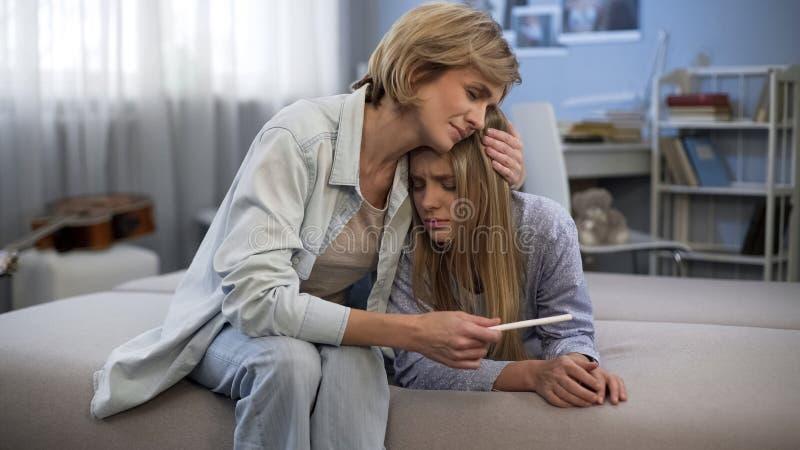 妈咪拥抱的生气女儿、少年怀孕、藏品测试、支持和关心 库存照片