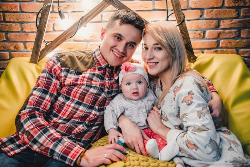 妈妈、爸爸和婴孩坐长沙发和容忍 免版税库存照片