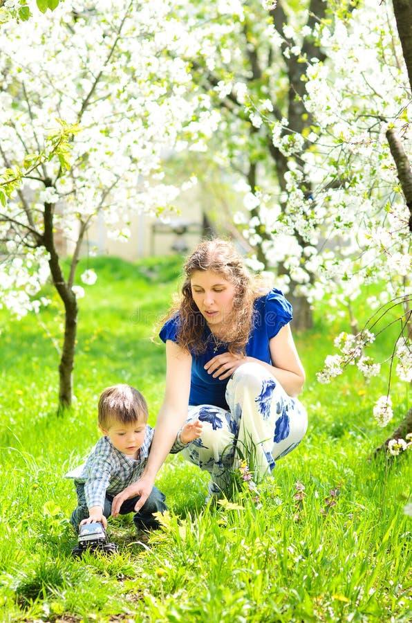 妈妈使用与草的小儿子 图库摄影