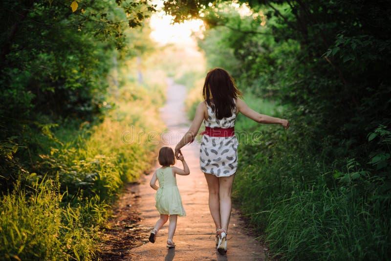 妈妈保留女儿的手并且走在自然的步行在日落光 免版税库存图片