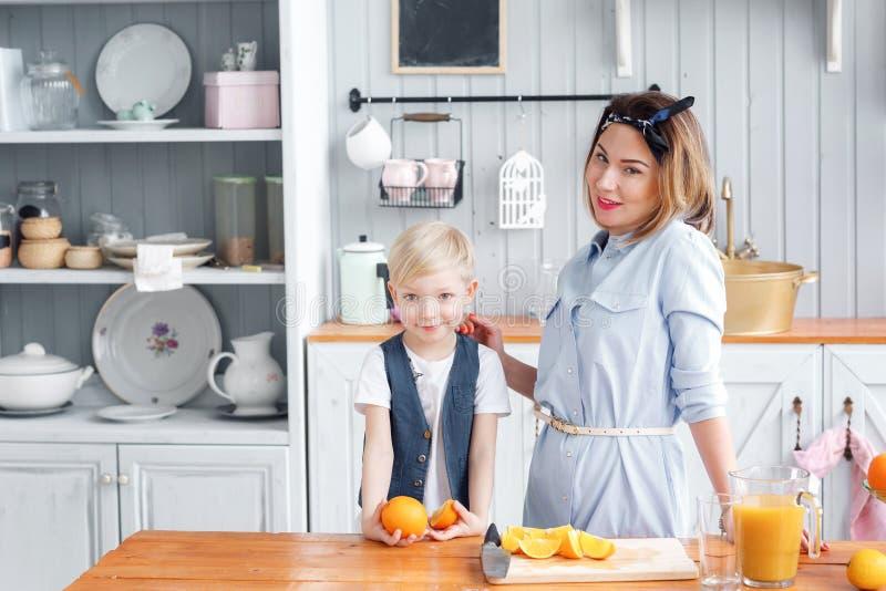 妈妈切果子给她的儿子 在一个木切板的切的桔子 早餐健康鲜美 免版税库存图片