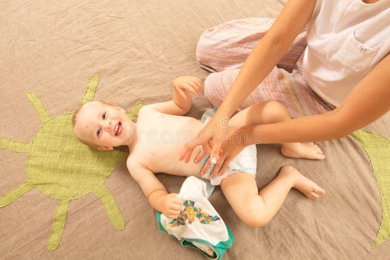妈妈变动滑稽的男婴婴儿尿布 库存照片