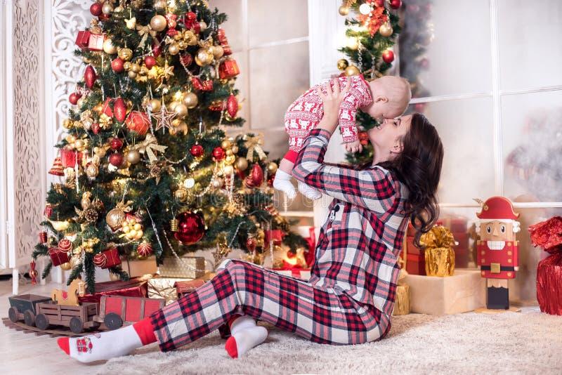 妈妈和一个小男孩在圣诞树附近使用新年 圣诞节的家庭传统 库存图片