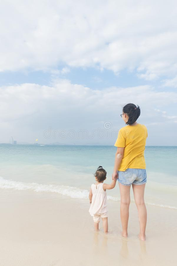 妈妈和一点女儿享受在海滩的悠闲时间 库存图片