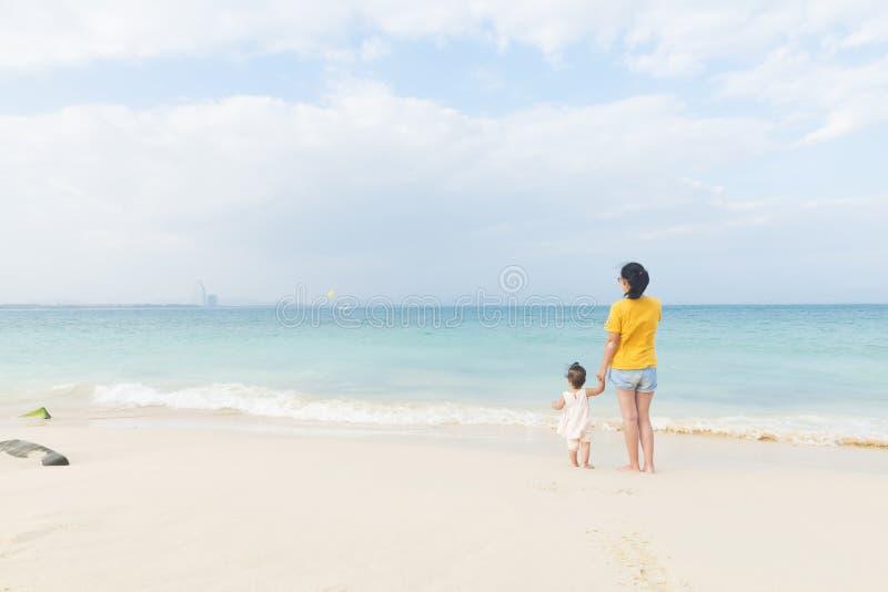 妈妈和一点女儿享受在海滩的悠闲时间 免版税库存图片