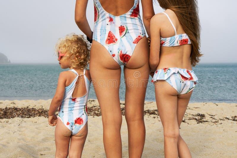 妈妈和两个女儿同一泳装的在一个含沙海海滩 有卷发的小女儿在桃红色太阳镜 免版税图库摄影