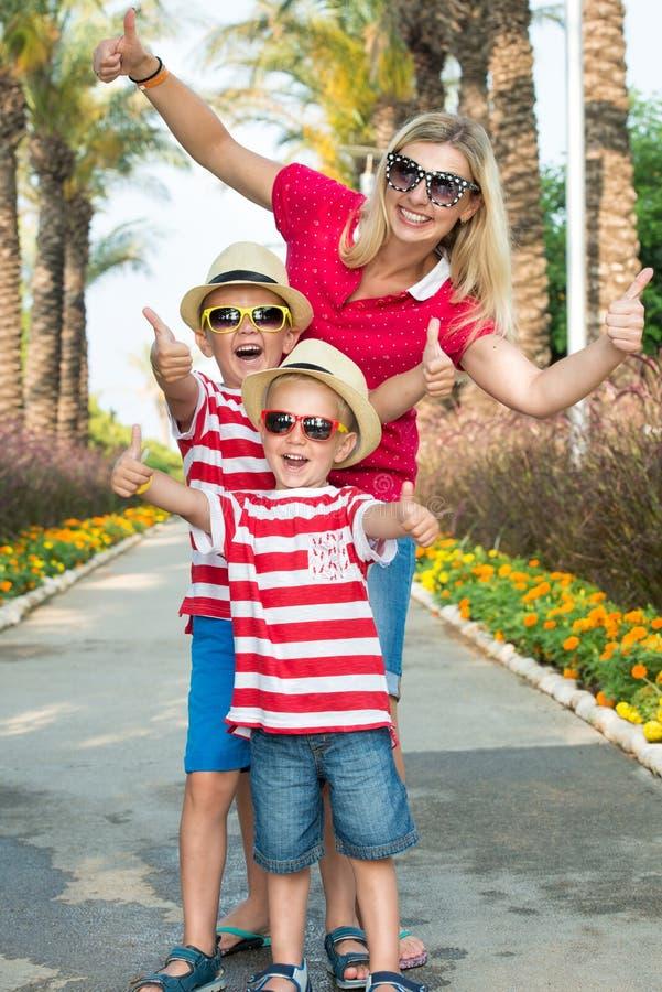 妈妈和两儿子走的太阳镜和帽子的通过棕榈树胡同  家庭暑假 库存照片
