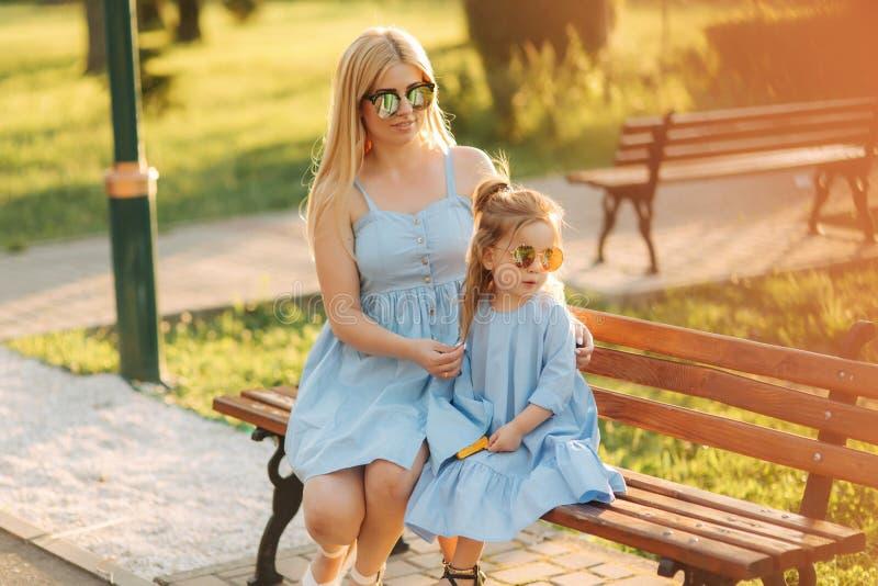 妈妈和他的小女儿坐一条长凳在公园 免版税图库摄影