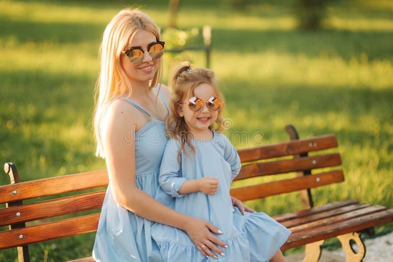 妈妈和他的小女儿坐一条长凳在公园 库存照片