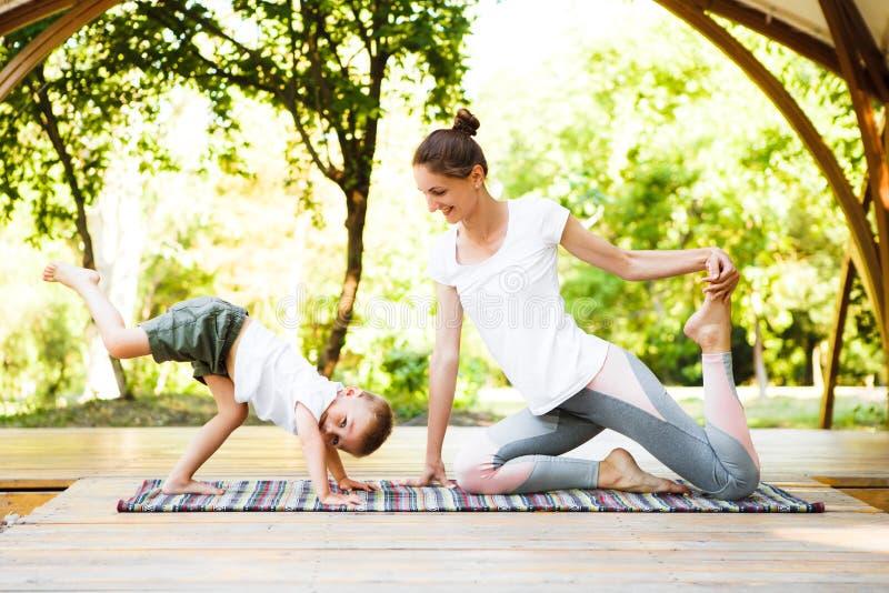 妈妈和儿子在公园实践瑜伽 免版税库存照片
