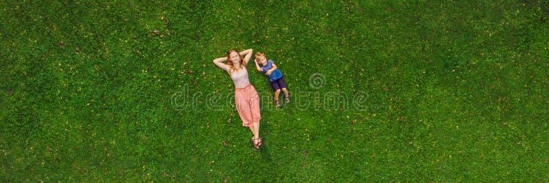 妈妈和儿子在草在公园,从寄生虫, quadracopter横幅长的格式的照片说谎 免版税库存图片