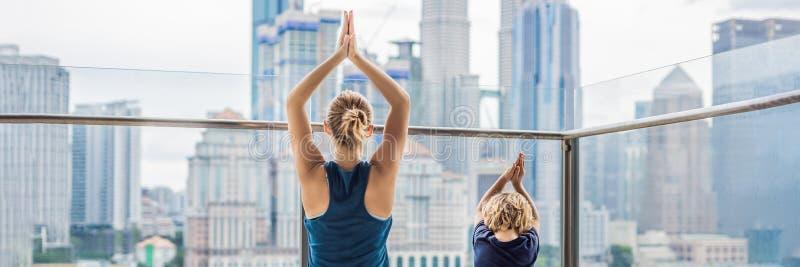 妈妈和儿子实践在阳台的瑜伽在一个大城市的背景中 有做早晨的孩子的体育妈妈在家解决 免版税库存图片