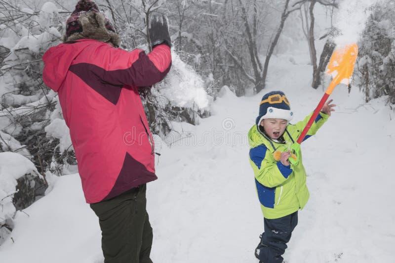 妈妈和儿子雪战斗的比赛 免版税库存照片