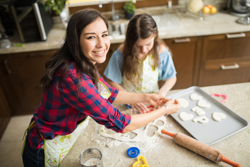 妈妈和女儿一起烘烤曲奇饼 免版税库存图片