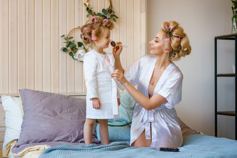 妈妈和女儿卷发的人的,互相做构成,幸福家庭 免版税库存照片