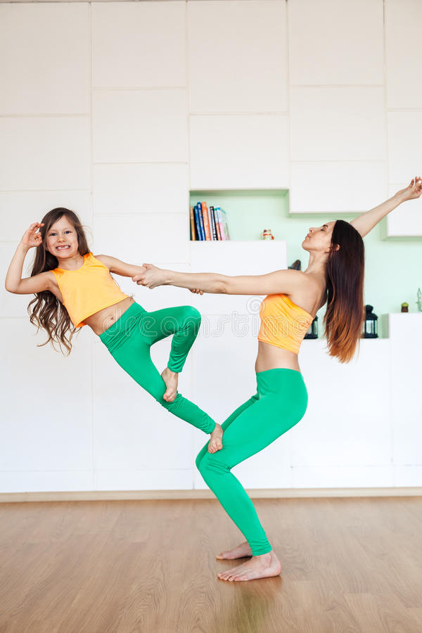妈妈和女儿参与瑜伽,在明亮的制服体育衣服 家庭瑜伽 库存图片