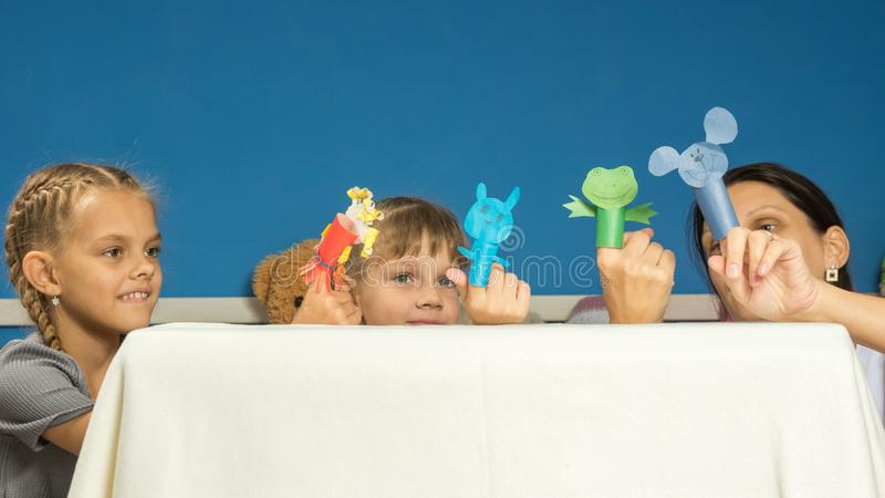 妈妈和女儿在一个手指的自制木偶剧院显示表现 库存图片