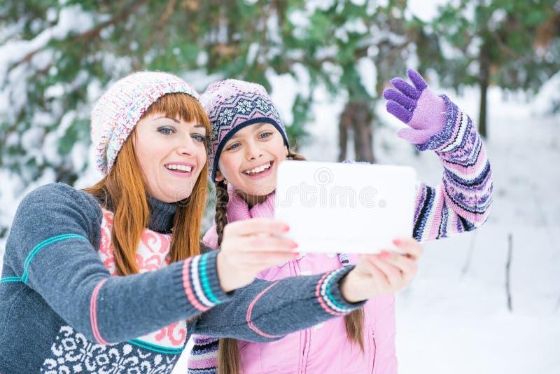 妈妈和女儿在冬天森林里被拍摄 免版税库存照片