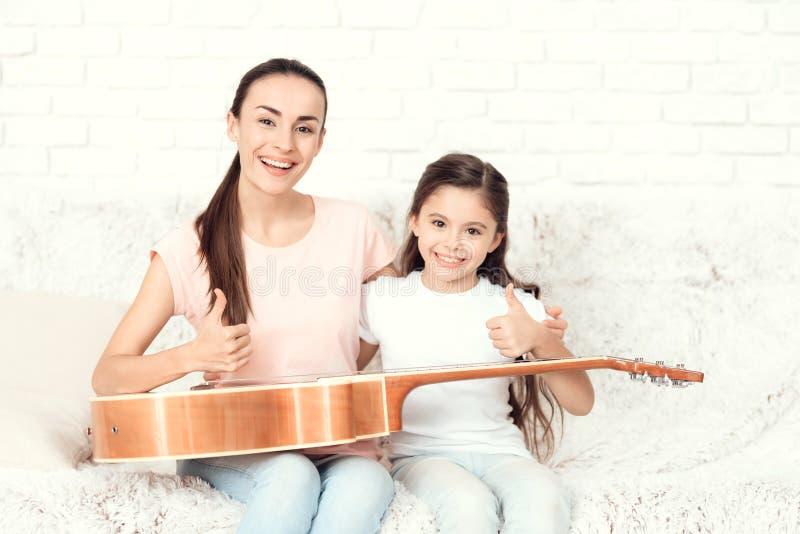 妈妈和女儿在家坐长沙发 他们有在他们的膝部的一把吉他 免版税库存照片