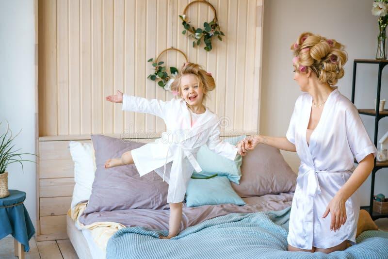 妈妈和女儿在床上玩 免版税库存照片